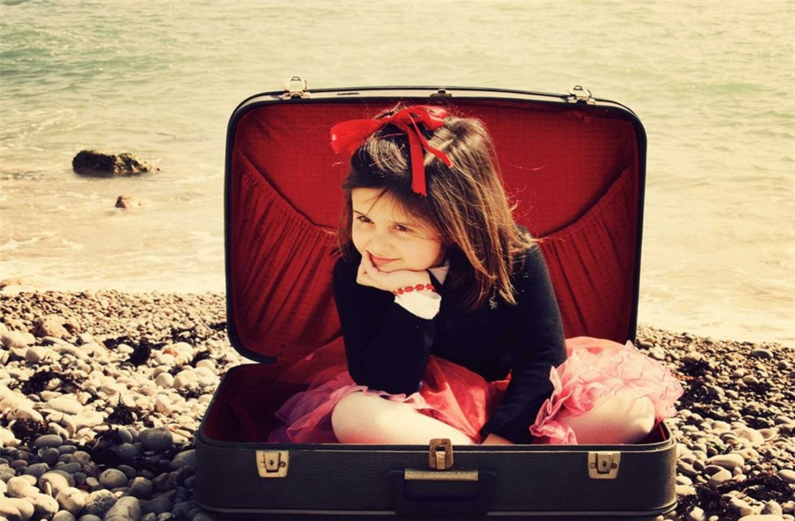 girl, a suitcase, sea, stones
